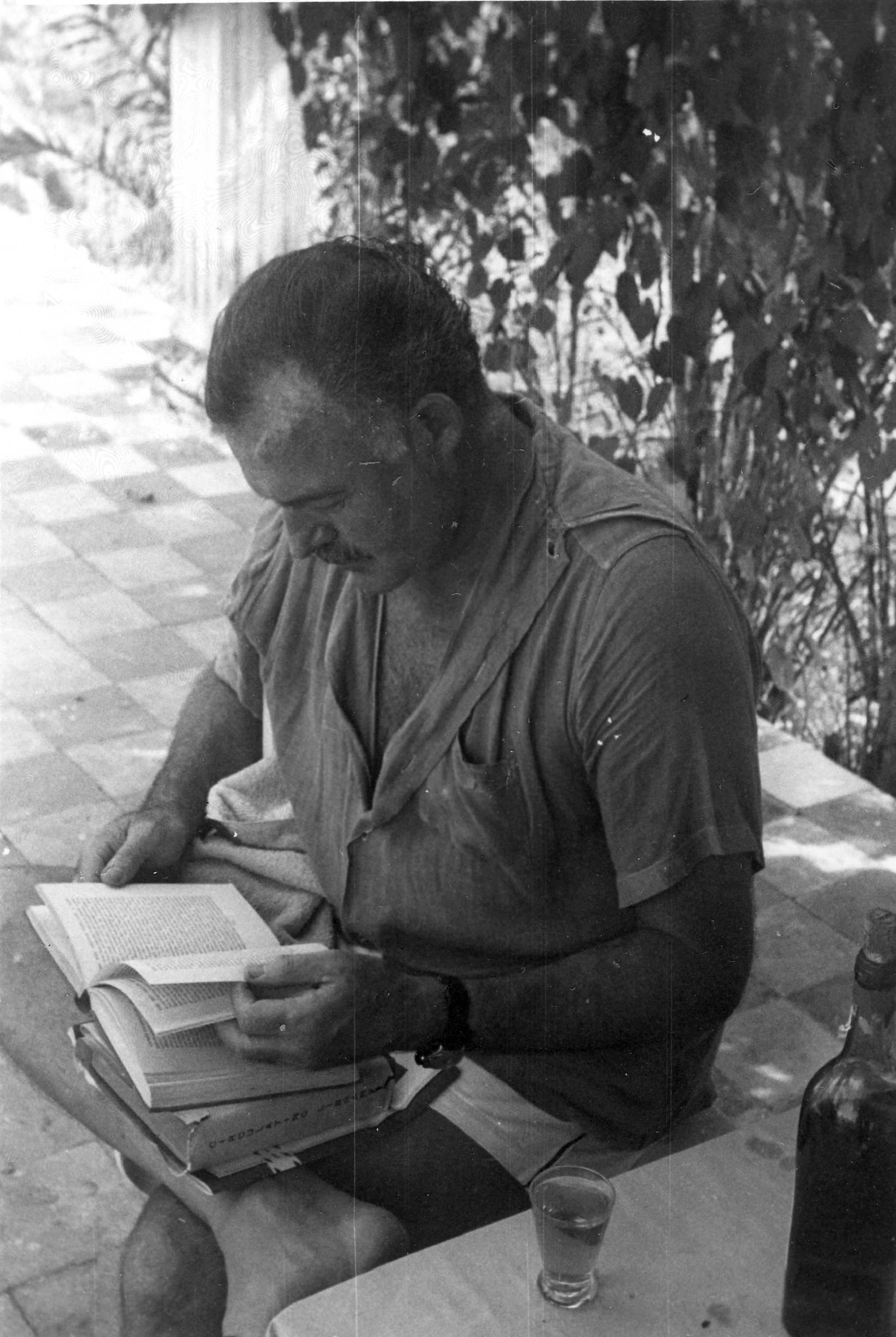 Ernest Hemingway reading outside his home, Finca Vigia, San Francisco de Paula, Cuba.